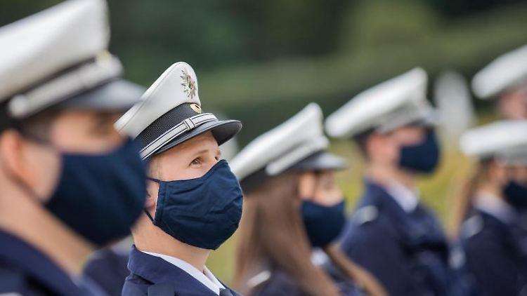 Kommissar-Anwärter stehen mit Stoffmasken bei der Vereidigungsfeier. Foto: Rolf Vennenbernd/dpa/Symbolbild