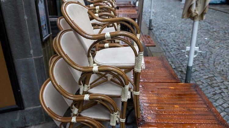 Tische und Stühle eines Cafés stehen auf einem Gehweg. Foto: Hendrik Schmidt/dpa-Zentralbild/dpa/Symbolbild
