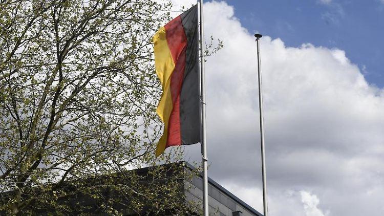 Eine Deutschlandflagge weht neben einer leeren Fahnenstange vor dem Rathaus von Solingen. Foto: Roberto Pfeil/dpa