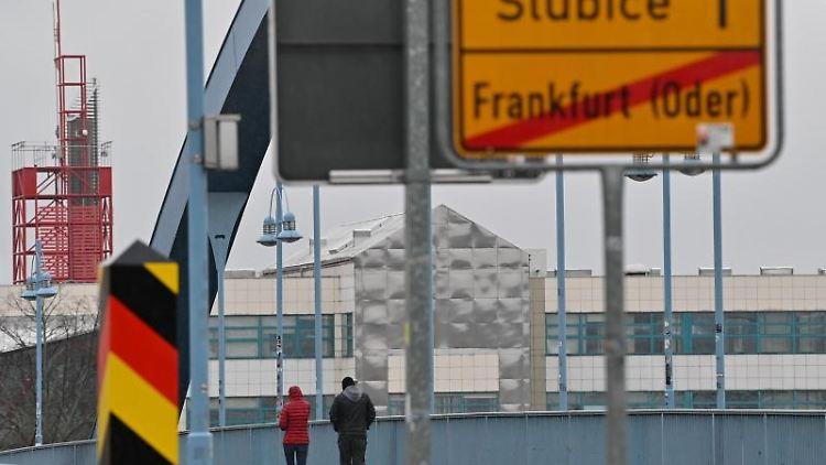 Zwei Personen gehen über den deutsch-polnischen Grenzübergang von Frankfurt (Oder) nach Slubice. Foto: Patrick Pleul/dpa-Zentralbild/dpa/Archivbild