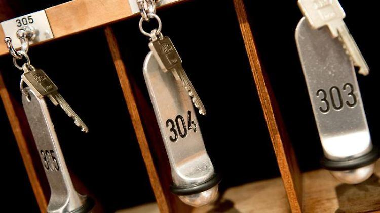 Zimmerschlüssel hängen in einem Hotel an einem Brett an der Hotelrezeption. Foto: Sven Hoppe/dpa