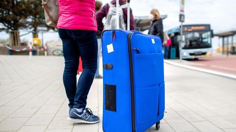 Eine Touristin steht mit ihrem Koffer an einer Bushaltestelle am Fährhafen auf Norderney. Foto: Hauke-Christian Dittrich/dpa/Archivbild