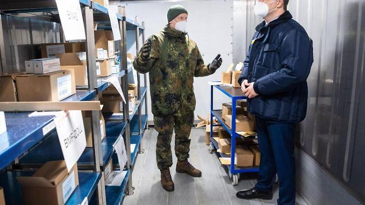 Gesundheitsminister Jens Spahn steht mit Oberstabsapotheker Julian Brederlow in einem Kühlcontainer. Foto: Sina Schuldt/dpa