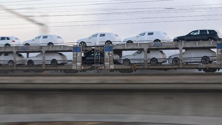 Ein Güterzug mit Neuwagen fährt am Morgen über eine Brücke. Foto: Robert Michael/dpa-Zentralbild/dpa