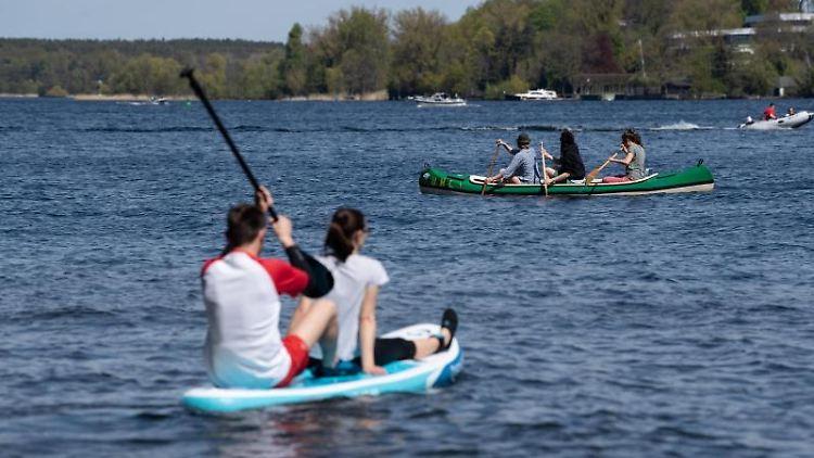 Menschen genießen auf SUPs und verschiedenen Booten bei Sonnenschein den See. Foto: Paul Zinken/dpa