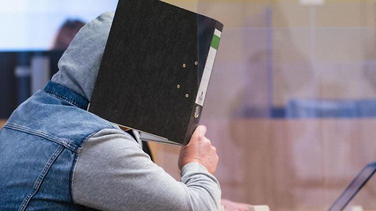 Der Angeklagte hält sich im Gerichtssaal einen Ordner vor das Gesicht. Foto: Nicolas Armer/dpa/Archiv