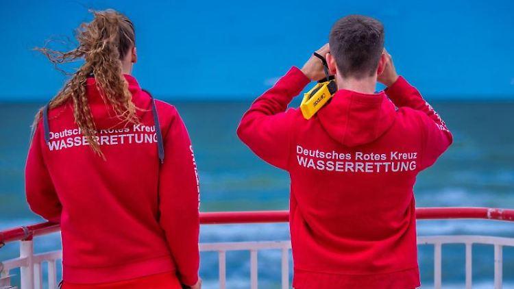 Rettungsschwimmer stehen auf einem Beobachtungsturm am Strand von Warnemünde. Foto: Jens Büttner/dpa-Zentralbild/dpa