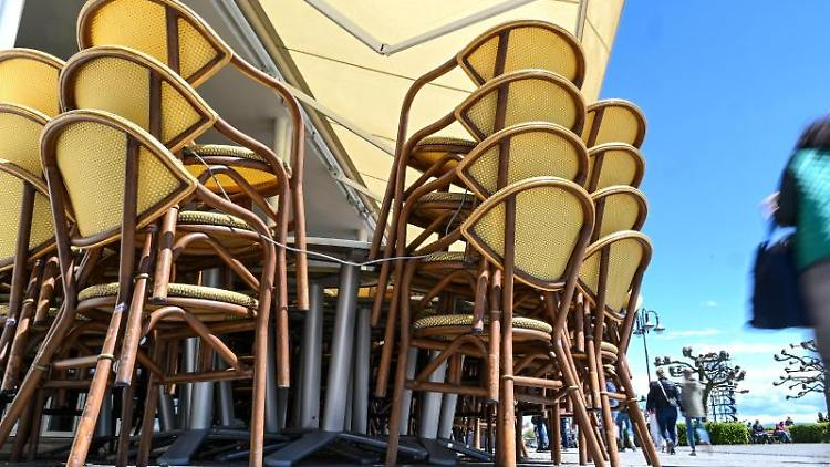 Tische und Bänke stehen aufgereiht an der Uferpromenade. Foto: Felix Kästle/dpa