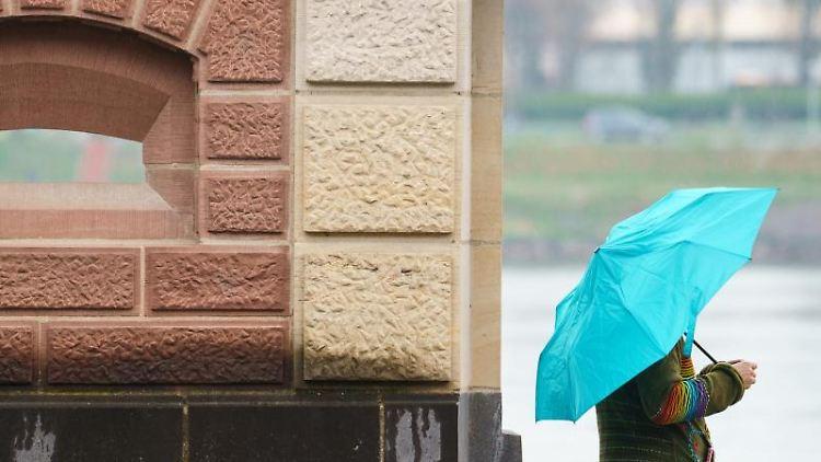 Eine Frau steht mit ihrem Regenschirm am Rheinufer. Foto: Andreas Arnold/dpa