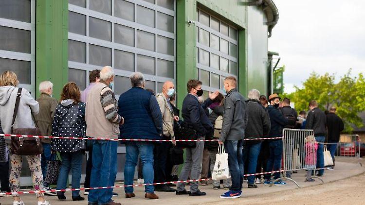 Parteimitglieder der AfD warten vor der Veranstaltungsstätte eines Sonderparteitages auf Einlass. Foto: Moritz Frankenberg/dpa/aktuell