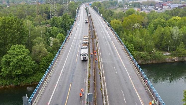 Lastwagen parken während eines Belastungstests auf der beschädigten A43-Emschertalbrücke. Foto: Marcel Kusch/dpa/aktuell