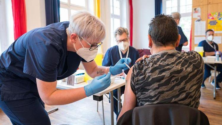 Ein mobiles Impfteam impft einen Mann mit dem Biontech/Pfizer-Impfstoff. Foto: Oliver Dietze/dpa/aktuell