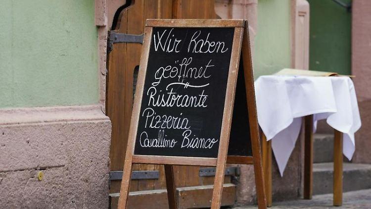 """Ein Schild mit der Aufschrift """"Wir haben geöffnet"""" steht vor einem Restaurant in der Innenstadt. Foto: Uwe Anspach/dpa/aktuell"""