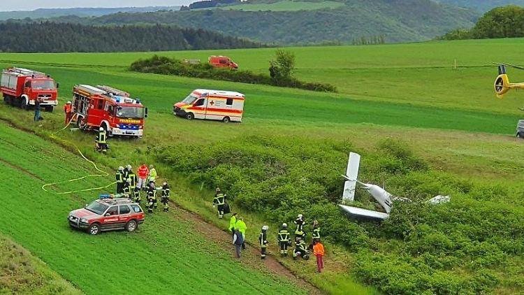 Ein Rettungshubschrauber und Rettungsfahrzeuge stehen an der Absturzstelle. Foto: Sebastian Schmitt/dpa/aktuell