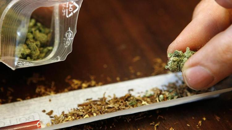 Ein Mann dreht sich einen Joint mit Cannabis. Foto: Daniel Karmann/dpa/Archivbild