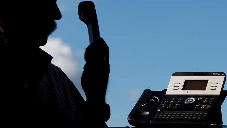 Ein Mann posiert mit einem Telefon. Foto: Julian Stratenschulte/dpa/Archivbild