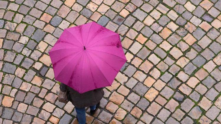 Eine Frau geht mit einem Regenschirm auf einer Straße mit Kopfsteinpflaster entlang. Foto: Sebastian Kahnert/dpa-Zentralbild/dpa/Archivbild