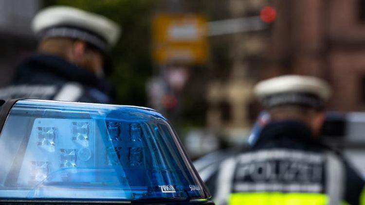 Polizeibeamte stehen zwischen zwei Einsatzfahrzeugen der Polizei. Foto: Philipp von Ditfurth/dpa/Symbol