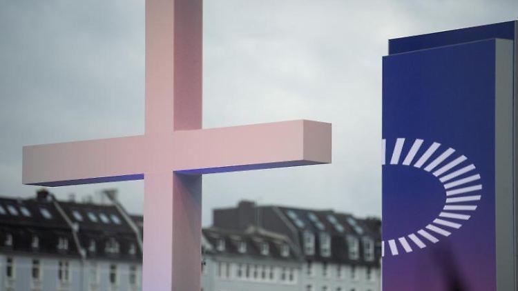 Ein Kreuz steht vor dem Schlussgottesdienst des 3. Ökumenischen Kirchentags (ÖKT) neben dessen Logo. Foto: Sebastian Gollnow/dpa/aktuell