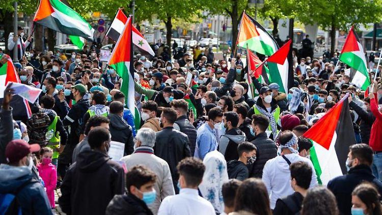 Teilnehmer der Demonstration stehen während einer Kundgebung zusammen. Foto: Philipp Schulze/dpa/aktuell