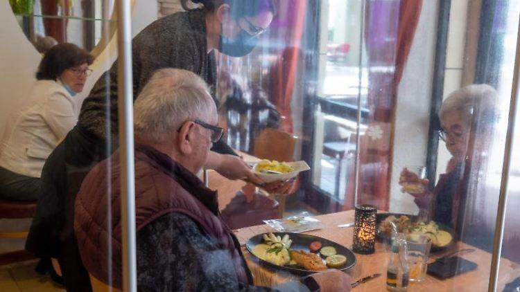 Eine Bedienung serviert im luxemburgischen Echternach im Innenbereich eines Restaurants das Essen. Foto: Harald Tittel/dpa/aktuell