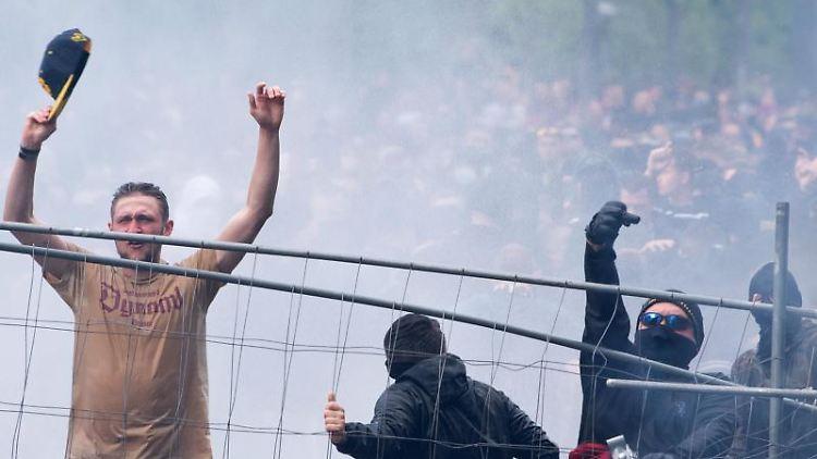 Fans errichten vor dem Stadion eine Blockade aus Bauzäunen. Foto: Sebastian Kahnert/dpa