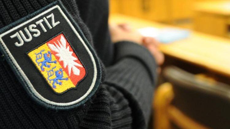 Ein schleswig-holsteinischer Justizbeamter steht im Landgericht im Sitzungssaal. Foto: Angelika Warmuth/dpa/Symbolbild