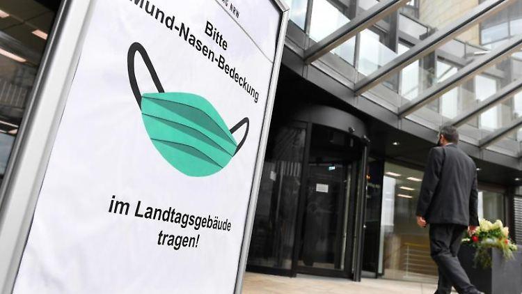 Ein Schild am Eingang des Düsseldorfer Landtages weist auf die Maskenpflicht im Gebäude hin. Foto: Roberto Pfeil/dpa/Archivbild