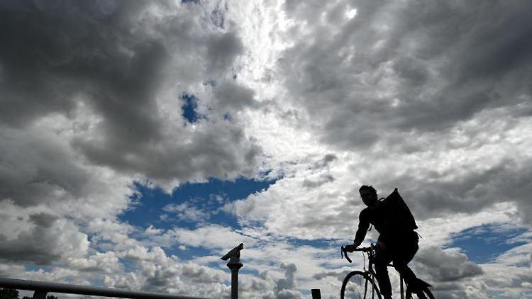 Ein Radfahrer ist bei dramatischer Bewölkung auf der Promenade am Mainzer Rheinufer unterwegs. Foto: Arne Dedert/dpa