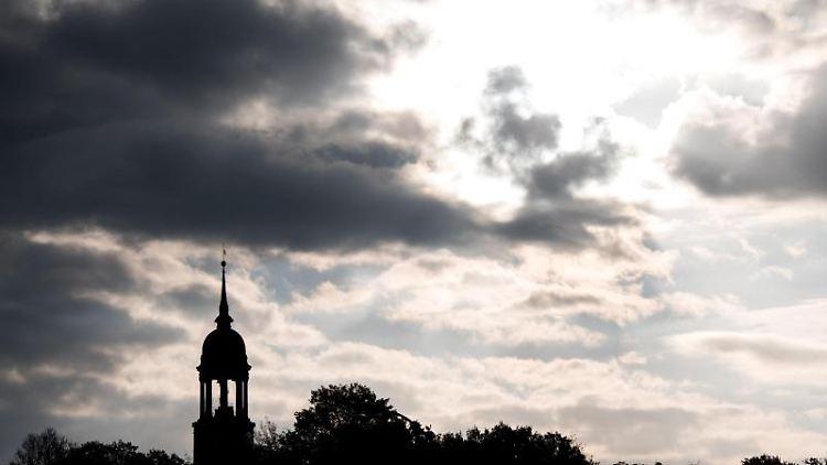 Die Sonne und Wolken sind hinter dem Turm der Hauptkirche St. Michaelis (Michel) zu sehen. Foto: Daniel Bockwoldt/dpa