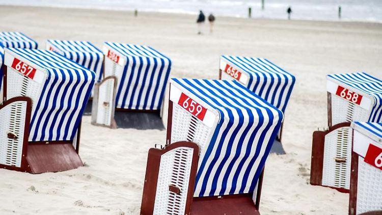 Strandkörbe stehen bei trübem Wetter im Sand am Weststrand von Norderney. Foto: Hauke-Christian Dittrich/dpa