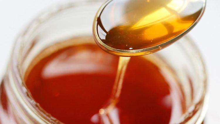 Honig fließt von einen Löffel zurück ins Honigglas. Foto: Oliver Berg/dpa/Symbolbild