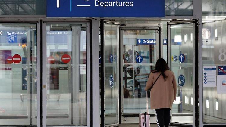 Eine Reisende geht in das Abflugterminal im Flughafen Düsseldorf. Foto: Henning Kaiser/dpa