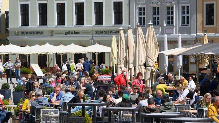Gäste sitzen in den Außenbereichen von Restaurants und Cafés. Foto: Robert Michael/dpa-Zentralbild/dpa/Archivbild