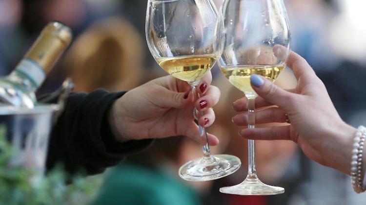 Frauen stoßen an einem Tisch im Außenbereich eines Lokals mit Weißwein an. Foto: David Young/dpa/Archivbild