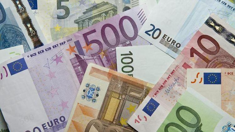 Zahlreiche Euro-Banknoten liegen auf einem Haufen. Foto: Daniel Reinhardt/dpa/Illustration