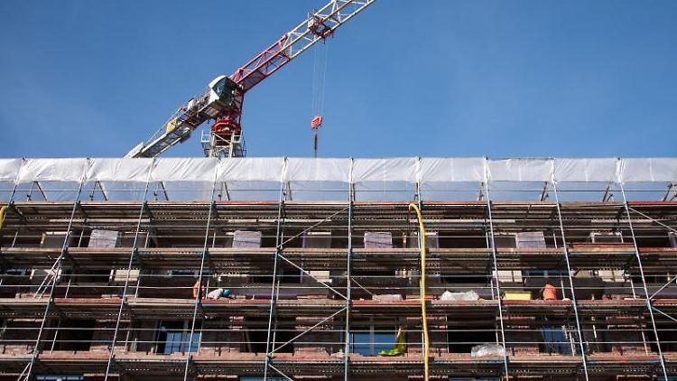 Ein Gerüst ist auf einer Baustelle an einem Neubau angebracht. Foto: Daniel Bockwoldt/dpa/Symbolbild