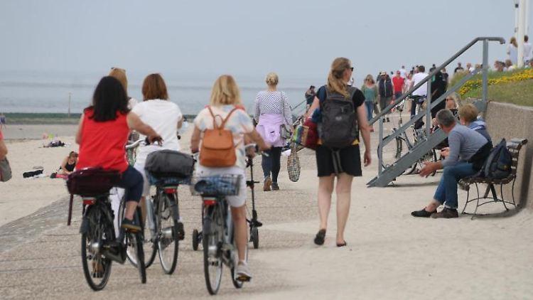 Menschen sind auf der Strandpromenade in Norderney unterwegs. Foto: Volker Bartels/dpa