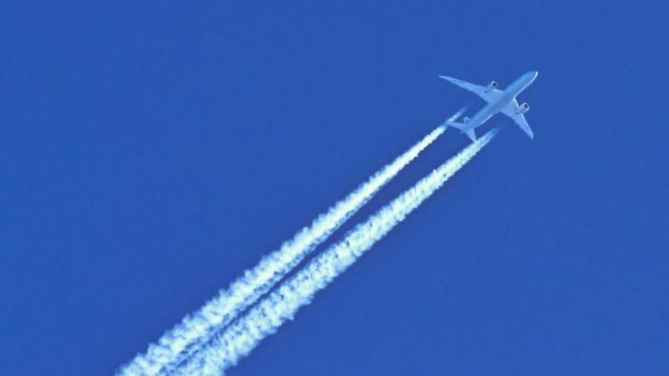 Am blauen Himmel fliegt ein Flugzeug und hinterlässt Kondensstreifen. Foto: Patrick Pleul/dpa-Zentralbild/dpa/Symbolbild