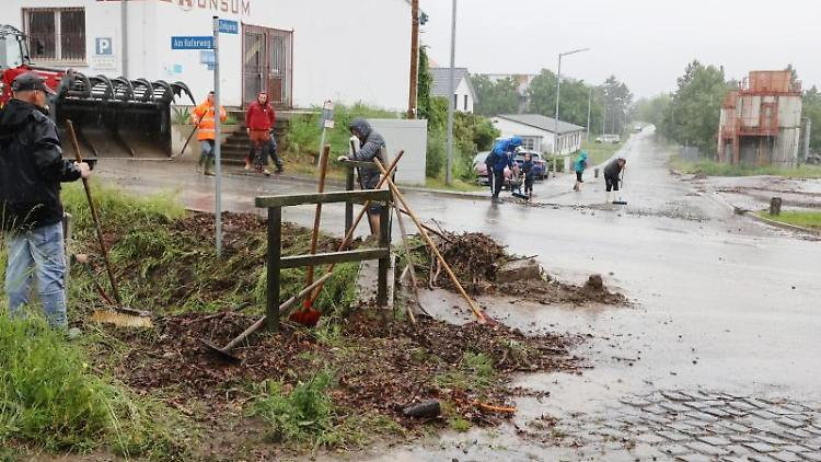 Helfer beseitigen Unrat aus einem Dorfbach nach heftigen Regenfällen am Sonntagmorgen. Foto: Bodo Schackow/dpa-Zentralbild/dpa