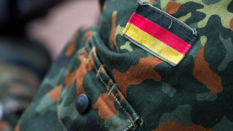 Die Deutschlandflagge ist auf der Uniform eines Bundeswehrsoldaten zu sehen. Foto: Monika Skolimowska/zb/dpa/Illustration