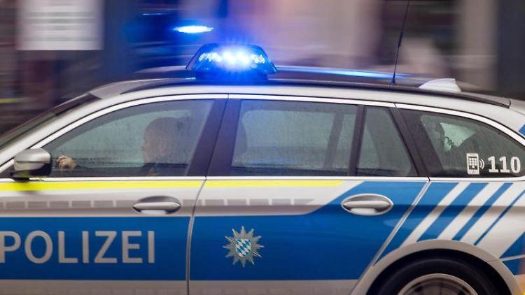 Ein Polizeiwagen fährt mit Blaulicht durch die Stadt. Foto: Peter Kneffel/dpa