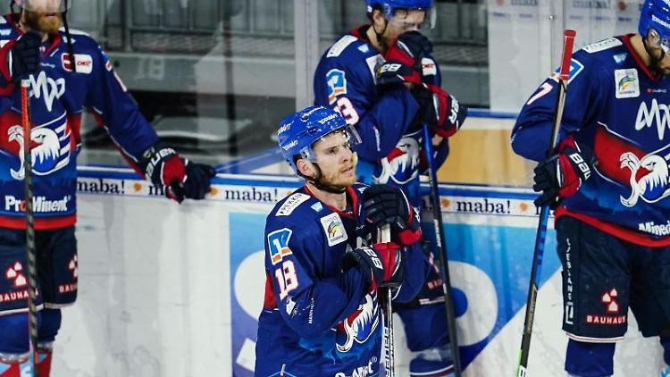 Mannheims Benjamin Smith (M, vorne) steht mit weiteren Spielern auf dem Eis. Foto: Uwe Anspach/dpa