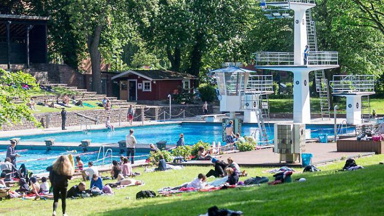 Badegäste geniessen einen Frühsommertag im Kaifu-Bad in Hamburg. Foto: Markus Scholz/dpa/Symbolbild