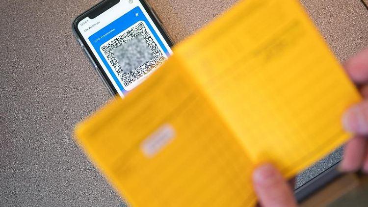 Ein Smartphone mit dem QR Code auf dem Tisch einer Apotheke. Foto: Oliver Dietze/dpa