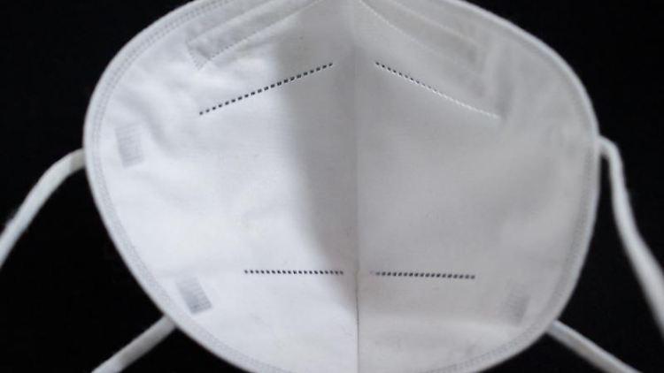 Eine FFP2-Maske liegt auf einem Tisch. Foto: Daniel Karmann/dpa/Symbolbild