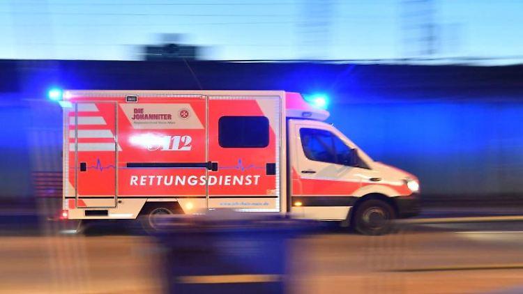 Ein Rettungswagen mit eingeschaltetem Blaulicht fährt auf einer Straße. Foto: Boris Roessler/dpa/Symbolbild