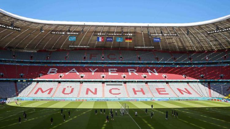 Die Spieler wärmen sich im Stadion auf. Foto: Christian Charisius/dpa