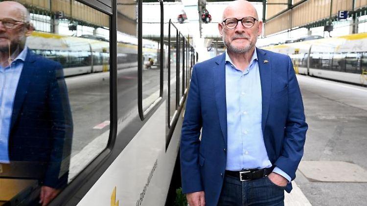 Baden-Württembergs Verkehrsminister Winfried Hermann steht vor einem Regionalzug. Foto: Bernd Weißbrod/dpa/archivbild
