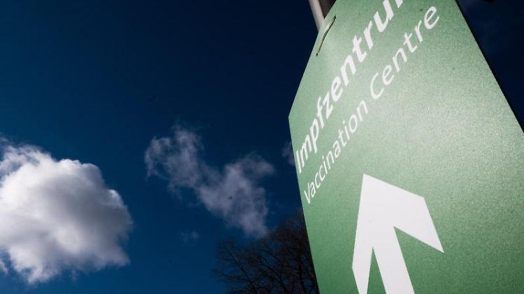 Ein Schild mit einem Pfeil weist den Weg zu einem Impfzentrum. Foto: Julian Stratenschulte/dpa/Archivbild